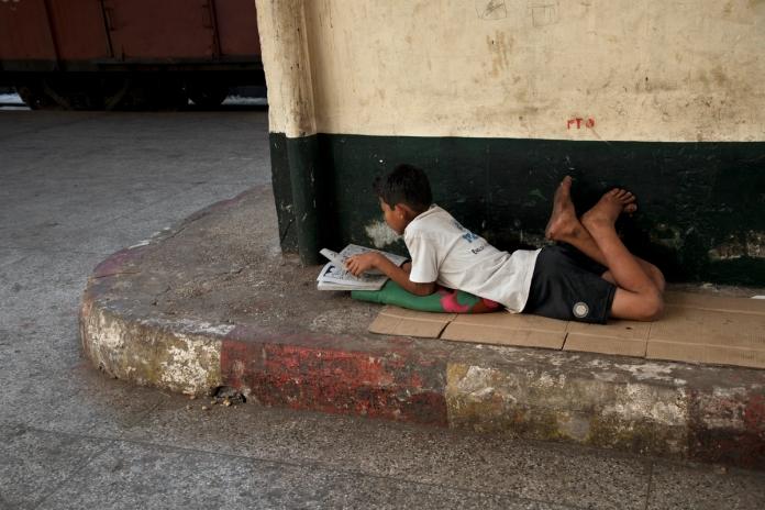 DSC_4524, Burma/Mynamar, 01/2014, BURMA-10711. A boy lies on the sidewalk reading. retouched_Ekaterina Savtsova 2/7/214